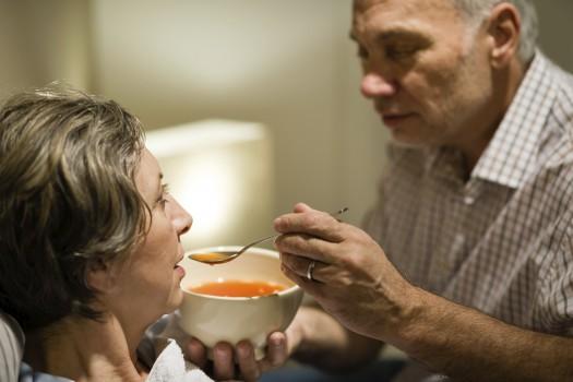 Caring senior man feeding his sick wife
